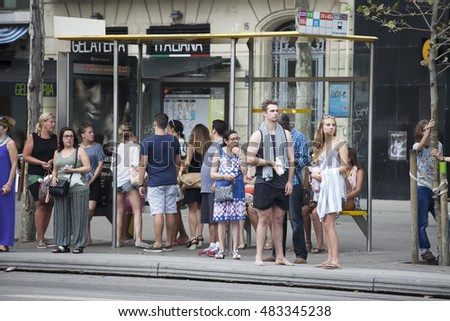 Barcelona, Spain - July 25, 2016 : Line of people waiting for bus at bus stop. Some of them returning from the beach.