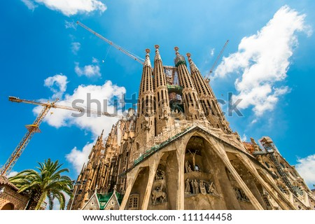BARCELONA, SPAIN - JULY 13: Sagrada Familia on July 13, 2012: La Sagrada Familia - the impressive cathedral designed by Gaudi, which is being build since 19 March 1882 and is not finished yet. - stock photo