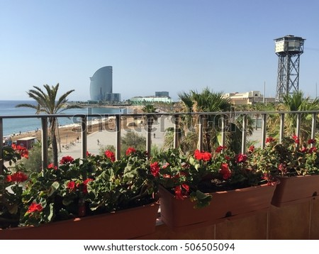 Barcelona, Spain - July 1st, 2016: View over the beach from a balcony in Plaza del Mar with W Hotel on the background.