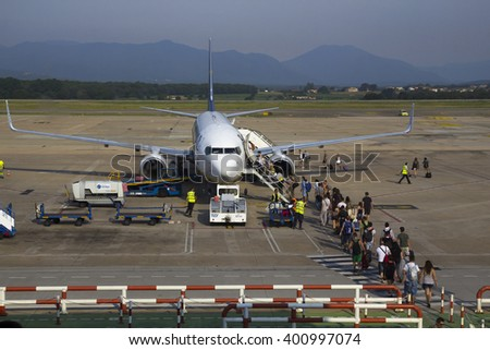 BARCELONA, SPAIN - JULY 28, 2014: Tourists ready to embark in a low cost airplane at the terminal of the airport of Barcelona, Spain, on July 28, 2014