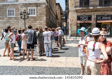 BARCELONA, SPAIN - 2 JULY: Tourists visits Sant Jaume square, where there is the catalan parliament and government. July 2, 2013.