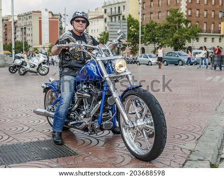 BARCELONA, SPAIN - JULY 05, 2014: Unidentified person with a Harley Davidson motorbike at an exhibition during BARCELONA HARLEY DAYS 2014, The event brought together over 12,000 motorcycles. - stock photo