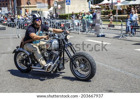 BARCELONA, SPAIN - JULY 05, 2014: Unidentified persons with a Harley Davidson motorbike at an exhibition during BARCELONA HARLEY DAYS 2014, The event brought together over 12,000 motorcycles.