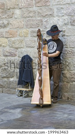 Barcelona, Spain - June 7, 2014 - A Catalan street musician performs in the Gothic Quarter in Barcelona, Spain. Catalan culture and music have become more popular with the Catalan movement in Spain.