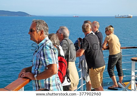BARCELONA  SPAIN - JUNE 2, 2015:  a group of people watching the skyline from a boat arriving at the port