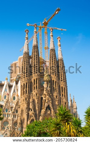 BARCELONA, SPAIN - JUNE 12, 2014: The Basilica of La Sagrada Familia against blue sky. Designed by Antoni Gaudi, its construction began in 1882 and is not finished yet