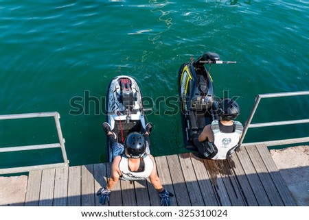 BARCELONA, SPAIN - JUNE 27. Two personal watercraft rider sit on the pier in the marina Port Vell, the old harbor of Barcelona on June 27, 2015. The city offers many opportunities for water sports - stock photo