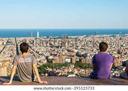 BARCELONA, SPAIN - JUNE 29. Young people are watching the skyline of Barcelona on June 29, 2015. The district Poblenou. The Sagrada Familia, the Towers of Port Olimpic and the harbor in Barcelona