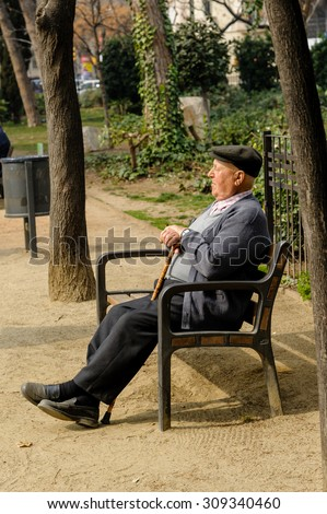 BARCELONA, SPAIN - MARCH 03, 2012: An old man resting on a park bench in Barcelona, Spain.