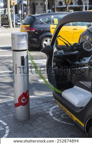 Barcelona, Spain - March 12, 2014: Loading electric bike in a public charging station on a street in Barcelona. The vehicle belongs to a rental company - stock photo