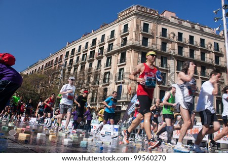 BARCELONA, SPAIN - MARCH 25:  unidentified athletes participate in the Barcelona marathon on March 25, 2012 in Barcelona, Spain. Over 15.000 runners took part in the 2012 edition. - stock photo