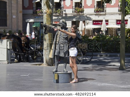 Barcelona, Spain - May 22, 2015: A female tourist stands for a picture with a living statue on La Rambla street in the Gothic Quarter in downtown Barcelona, Spain on May 22, 2015.