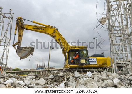 Barcelona, Spain - 12 May, 2014: excavator placing sand or debris on a truck with the Sagrada Familia in the background. The driver is focused on work - stock photo