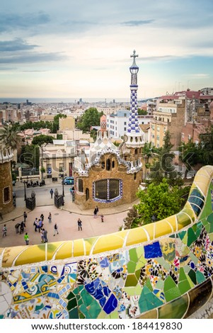 BARCELONA, SPAIN - MAY 31, 2013: Famous colorful ceramic mosaic bench of park Guell, with entrance pavilion on the background and designed by Antonio Gaudi