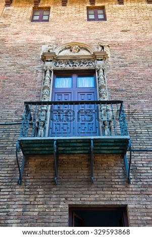 BARCELONA, SPAIN - MAY 02: Low Angle View of Balcony with Ornate Railing and Doorway on Exterior of Brick Building Wall, Barcelona, Spain. May 02, 2015. - stock photo