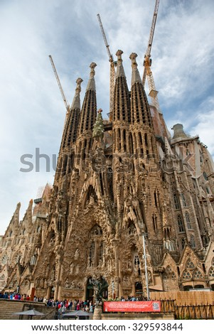 BARCELONA, SPAIN - MAY 02: Low Angle View of Facade Exterior of Sagrada Familia Church with Crowds of Tourists Gathered in Front, Barcelona, Spain. May 02, 2015. - stock photo