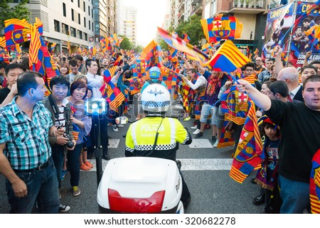 BARCELONA, SPAIN - 15 MAY 2013: meeting fans of FC Barcelona with team on the club bus, in the middle of a policeman on a motorcycle