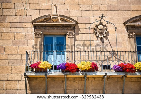 BARCELONA, SPAIN - MAY 02: Stone townhouse with Art Nouveau windows with carved architraves and an iron railing on the exterior balcony, Poble Espanyol, Barcelona, Spain. May 02, 2015 - stock photo