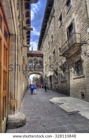 Barcelona, Spain - May 24, 2015: Tourists in Del Bisbe street in the Barri Gotic historical area in Barcelona, Spain on May 24, 2015. - stock photo