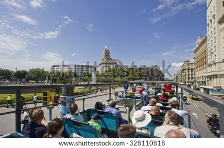 Barcelona, Spain - May 25, 2015: Tourists sit on the upper deck of a double decker bus on Placa de Catalunya in Barcelona, Spain on May 25, 2015. - stock photo