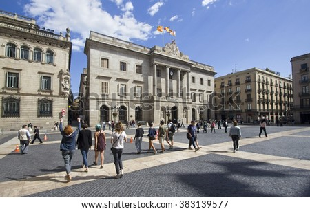 Barcelona, Spain - May 21, 2015: Tourists walk on the Placa de Sant Jaume in front of the City Halll of Barcelona, Spain on May 21, 2015.