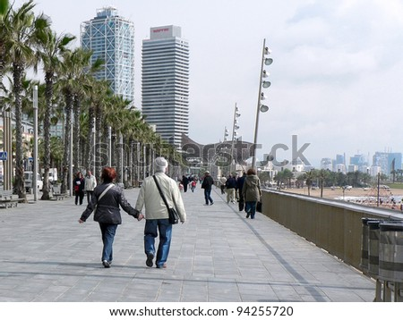 "BARCELONA, SPAIN - MAY 7: Unidentified couple strolls along the Mediterranean seashore on May 7, 2010. The fish-shaped sculpture is ""Peix"" (fish in Catalan) by noted artist Frank Gehry."