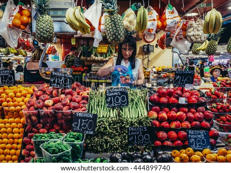 Barcelona, Spain - May 26, 2015. Woman sells fruits and vegetables at public market called La Boqueria, foremost tourist landmarks in Barcelona - stock photo