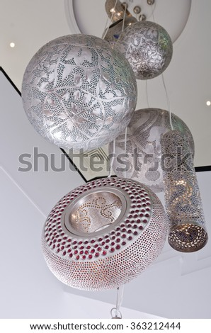 Barcelona, Spain, 05/06/2014, Metal light shade with intricate floral pattern hanging in a clean white vintage boutique