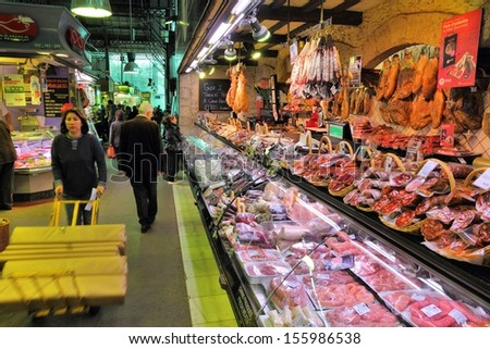 BARCELONA, SPAIN - NOVEMBER 6: People visit Boqueria market on November 6, 2012 in Barcelona, Spain. Tripadvisor says it is best shopping destination in Barcelona, the most visited city in Spain. - stock photo