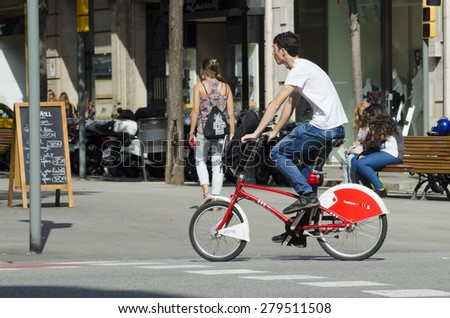 BARCELONA, SPAIN - OCTOBER 7, 2014: A young man in a rental bike, stroll along one of the busiest streets of the city, next to a city bus stand. - stock photo