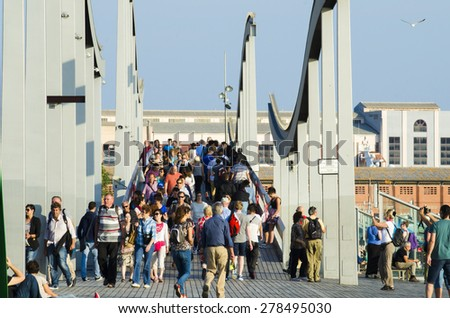 BARCELONA, SPAIN - OCTOBER 6, 2014: Crowds of tourists through one of the bridges near the Maremagnum, Marina City. - stock photo