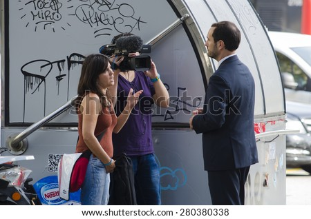 BARCELONA, SPAIN - OCTOBER 7, 2014: Some journalists conducted an interview with a video camera, a man in one of the streets of their city. - stock photo
