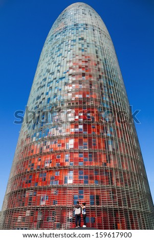 BARCELONA, SPAIN - OCTOBER 13: Torre Agbar with an unidentified couple on October 13, 2013 in Barcelona. the 142 meters high tower was designed by Jean Nouvel and should be a homage to Antoni Gaudi. - stock photo