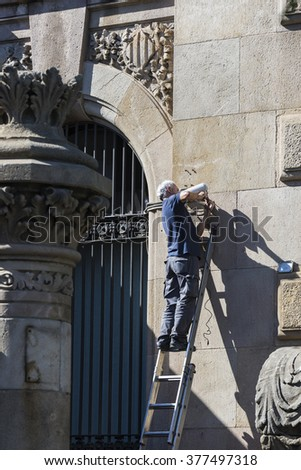 Barcelona, Spain - October 22, 2014: Worker installing a security camera on the wall of a building