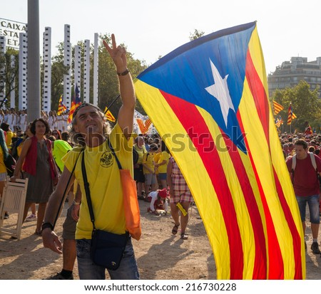 BARCELONA, SPAIN - SEPT. 11: Man carrying a big republican flag makes the sign of victory in the rally for the independence during the National Day of Catalonia on Sept. 11, 2014 in Barcelona, Spain.