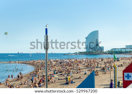 BARCELONA. SPAIN - SEPTEMBER 17;Barcelonetta Beach architecturally modern W Hotel in distance, para-glider above cargo ships on horizon sunbathers along sandy beach, September 17. 2016 Barcelona Spain
