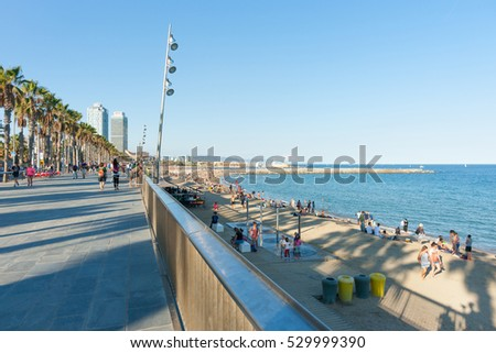 BARCELONA, SPAIN - SEPTEMBER 17; Barcelonetta Beach late afternoon with long shadows of palm trees across promenade and beach, two office and hotel buildings September 17, 2016; Barcelona Spain