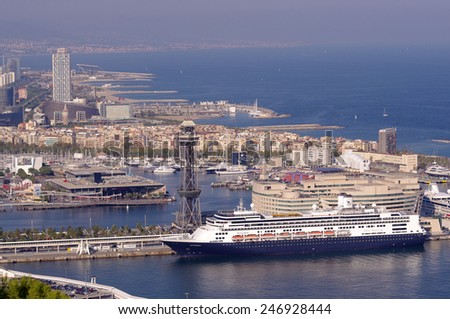 BARCELONA, SPAIN - SEPTEMBER 28, 2011: Large cruise ship in the Port of Barcelona. Daytime view from Montjuic hill in Barcelona, Spain.  - stock photo