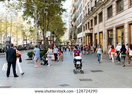 BARCELONA, SPAIN - SEPTEMBER 13:  people walk daily by street in downtown of Barcelona on September 13, 2012.  More than 7 million visitors were in Barcelona in 2012. - stock photo