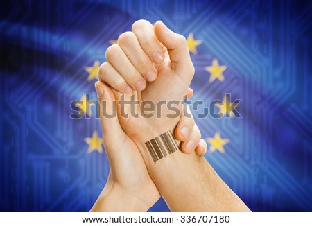 Barcode ID number on wrist of a human and national flag on background - European Union - stock photo