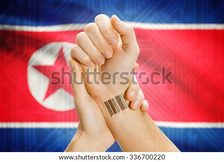 Barcode ID number on wrist of a human and national flag on background - North Korea