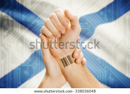 Barcode ID number tatoo on wrist and Canadian province flag on background - Nova Scotia