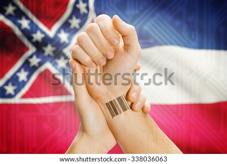 Barcode ID number tatoo on wrist and USA statesl flag on background - Mississippi