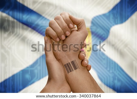 Barcode ID number tatoo on wrist of dark skin person and Canadian province flag on background - Nova Scotia