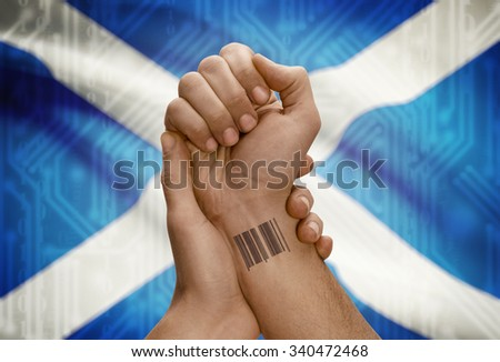 Barcode ID number tattoo on wrist of dark skinned person and national flag on background - Scotland
