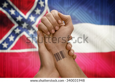 Barcode ID number tattoo on wrist of dark skinned person and USA states flag on background - Mississippi