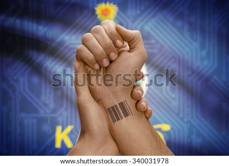 Barcode ID number tattoo on wrist of dark skinned person and USA states flag on background - Kansas - stock photo