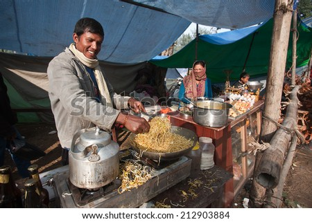 Bardia, Nepal - January 16, 2014: Street seller cooking nepali local food during Maggy festival fair in Bardia, Nepal