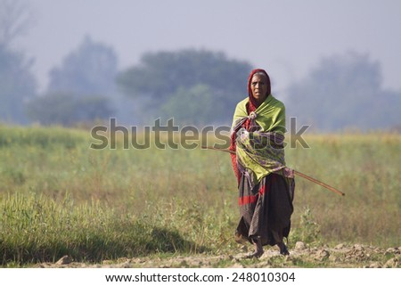 Bardia, Nepal - March 14, 2014: Old tharu woman walking in nepali countryside. Tharu people are one of the most poor cast of Nepal. - stock photo