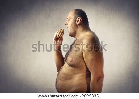 Bare-chested fat man eating a hamburger